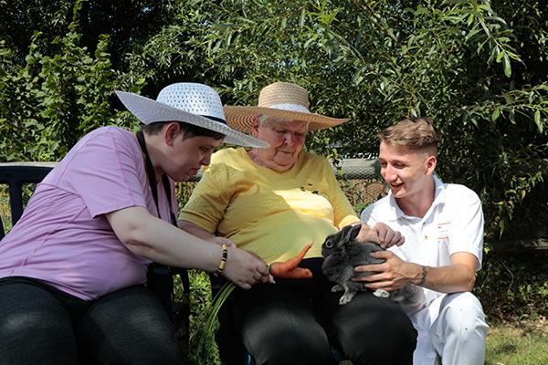 Zwei Seniorinnen, ein Pfleger und ein Kaninchen