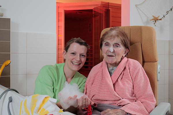 Mitarbeiterin und Seniorin im Pflegebad mit Schaum