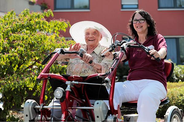 Seniorin und Mitarbeiterin auf dem Therapiefahrrad